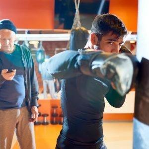 Selección de personas. Man boxing bag with trainer on workout